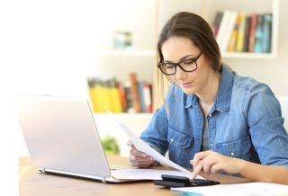 Une femme devant son PC avec une calculette